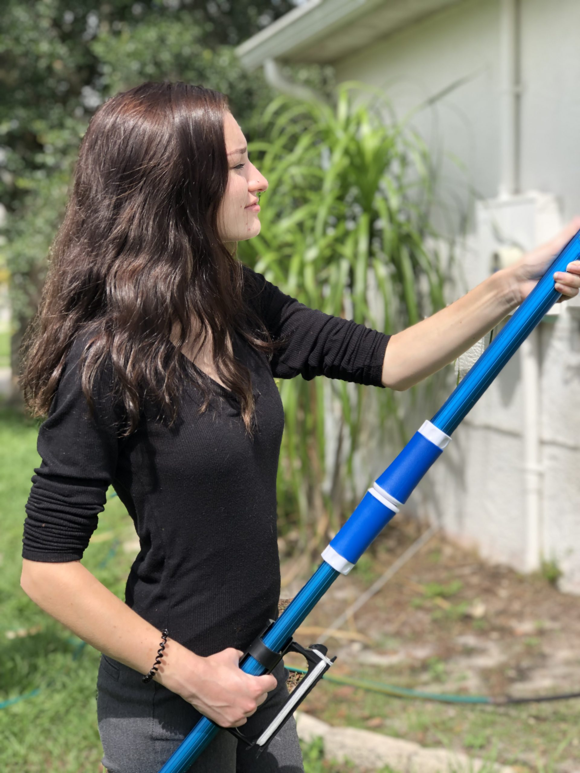 Young lady cleaning gutters using Gutter Fingers gutter cleaning tool