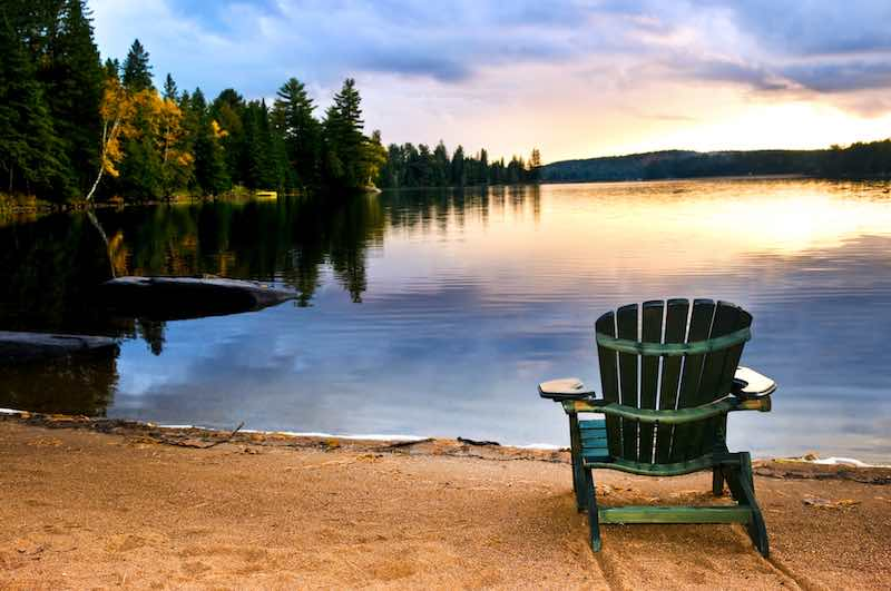 Recliner chair on the lake shore with a sunset in the horison