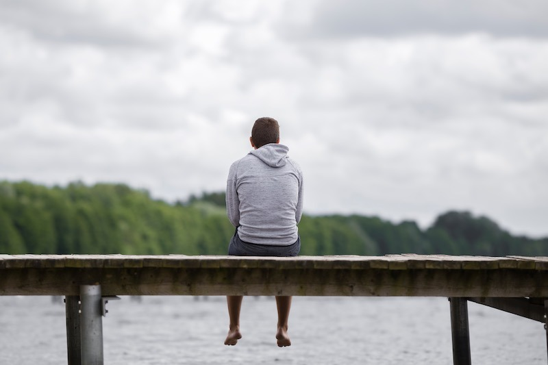 Young man sitting on a pontoon  near a beautiful lake listening to the sounds